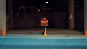 """""""stop"""" sign on the side of the road with traffic cones"""